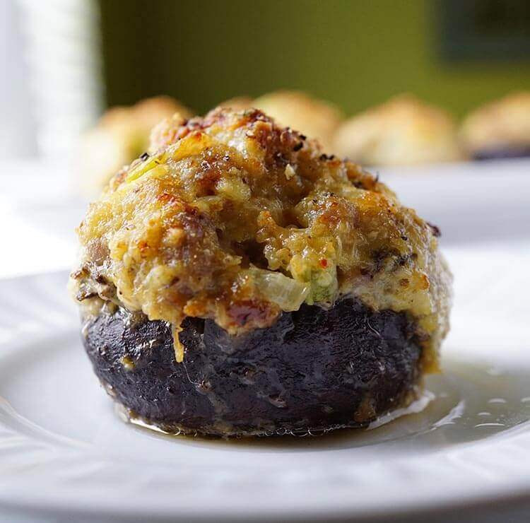 How Long To Cook Stuffed Mushrooms  Baked stuffed mushrooms on a white plate The top of the