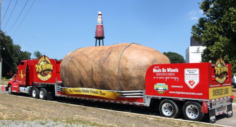 Worlds Biggest Potato  Gigantic potato rolls up next to world's largest ketchup